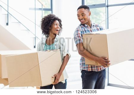 Smiling young couple holding a carton in their new house