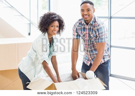 Portrait of young couple unpacking carton boxes in their new house