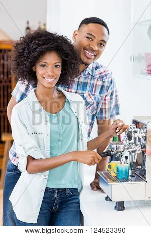 Portrait of young couple preparing coffee from coffeemaker at home
