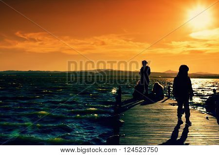 Bright and vinbrant scene on waterscape with people on pier and mountains far
