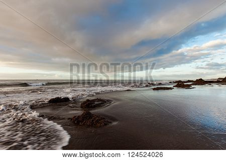 Summer sunrise seascape on tropical island Tenerife, Canary in Spain. Playa de La Tejita beach view on atlantic ocean and Punta Roja rock.