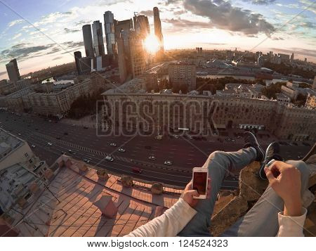 Feet of man with phone sitting on high building in modern city at sunny day