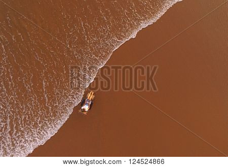 Top view of a air shooting from drone of young woman wanderer is keyboarding on laptop computerwhile is lying on a lounger on the beach and using high speed internet connection by broadband usb modem