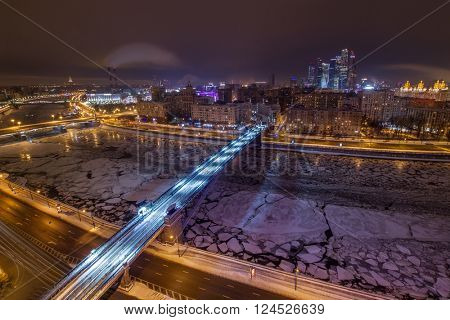 Smolensky Metro Bridge and river with ice at night in Moscow, Russia, long exposure