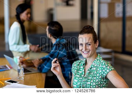 Young woman holding spectacles smiling at camera while colleagues interacting in the background