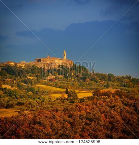 View to the Tuscany medieval city Pienza with colorful trees and fields, at sunset
