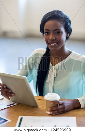 Portrait of businesswoman holding disposable coffee cup and digital tablet at her desk in the office
