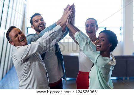 Colleagues doing high five in the office