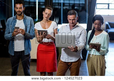 Team of colleagues using mobile phone, digital tablet and laptop in the office