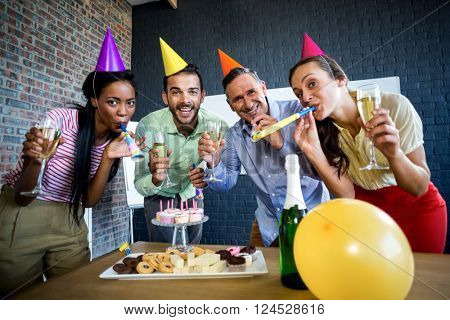 Portrait of colleagues celebrating birthday in the office