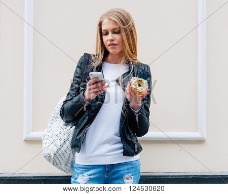 Portrait of a beautiful young sexy woman eating a donut, looks at her smart phone on the street European city