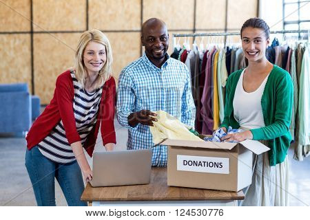 Portrait of colleagues sorting clothes from donation box in the office