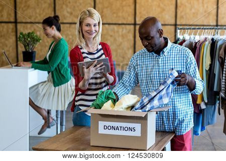 Colleagues using digital tablet while sorting clothes from donation box in the office