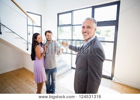 Real-estate agent giving house keys to couple in their new home