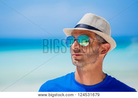 Portrait of a man in the sunglasses and hat on the beach