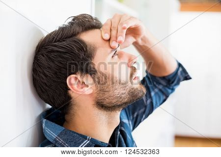 Tensed man leaning on wall at home