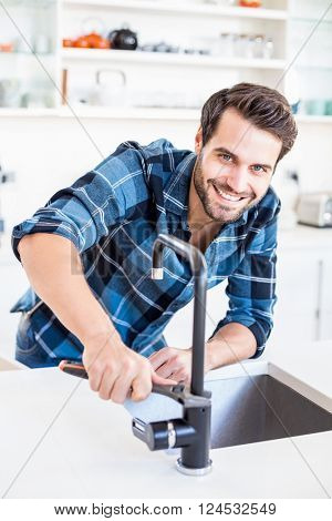 Portrait of happy man fixing tap with tool in the kitchen at home