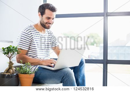 Happy man sitting on steps using laptop at home