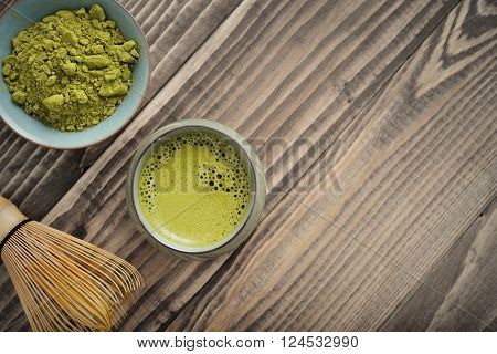 Organic Green Matcha Tea in a small cup with bamboo whisk top view
