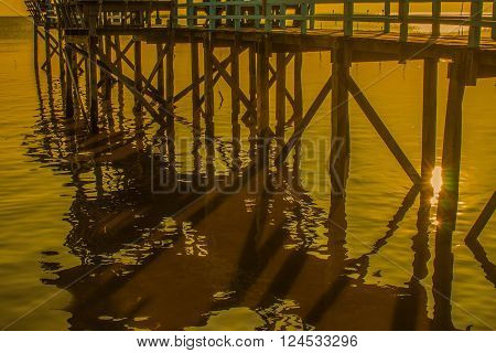 Wooden bridge and the reflection of the sun's surface in the evening.