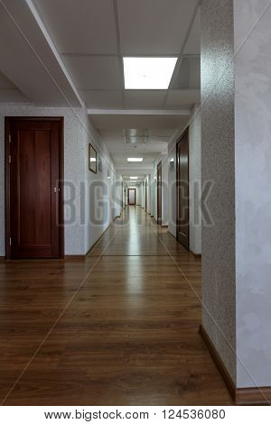 modern generic long office hallway with wooden floors and white painted walls