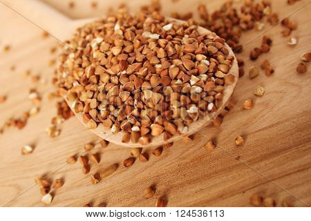 Close-up of buckwheat grains lie in a wooden spoon