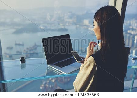 Young Asian businesswoman is holding mobile phone with blank display while is sitting in skyscraper building at the table with open laptop computer with empty copy space screen for your advertising