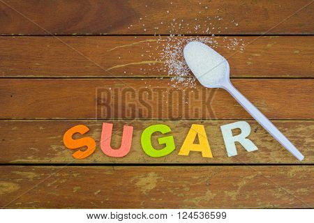 Scattered refined sugar and spoonful of refined sugar with word SUGAR on wooden table