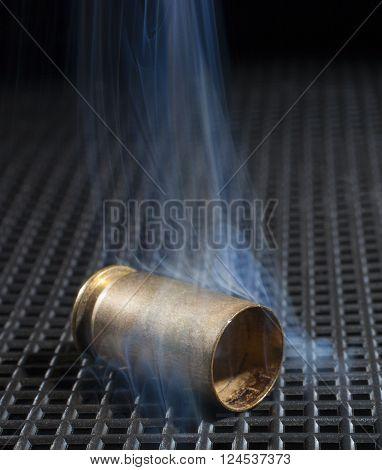 Brass from a semi automatic handgun with smoke around