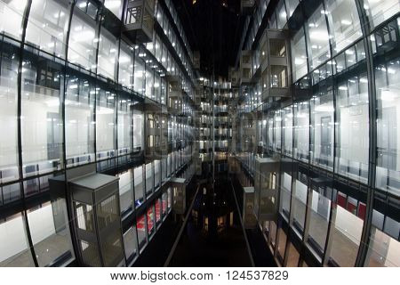 Beautiful illuminated windows with relfection in glass - modern building at night in city