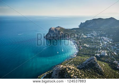 Beautiful coast of sea with rocks, town and mountains at hot summer day