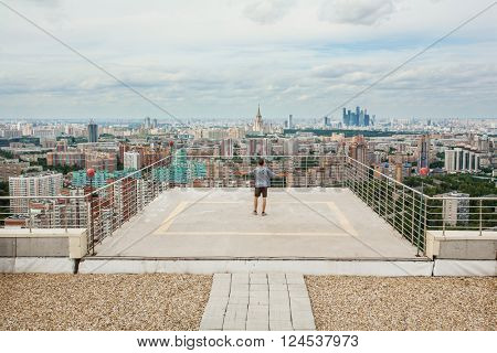 Man stands on roof of high building with railing at summer day in Moscow, Russia