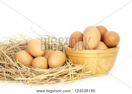 Fresh eggs on rice straw on white backgound