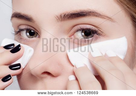 Woman using cotton pad. Happy smiling beautiful young woman cleaning skin by cotton pad. light background. Beautiful Spa Woman Smiling. Perfect Fresh Skin. Youth and Skin Care Concept, photo half