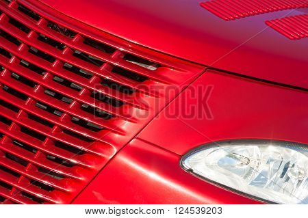 cherry red vehicle grille in bright sunlight