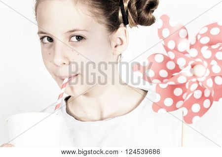 cute funny girl blowing a pinwheel in retro style