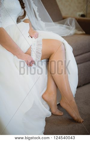 The bride wears a wedding garter on the leg on the bed