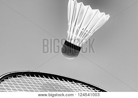Badminton racket striking shuttlecock closeup and high up