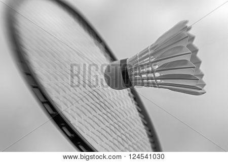 Badminton racket striking shuttlecock high up and closeup