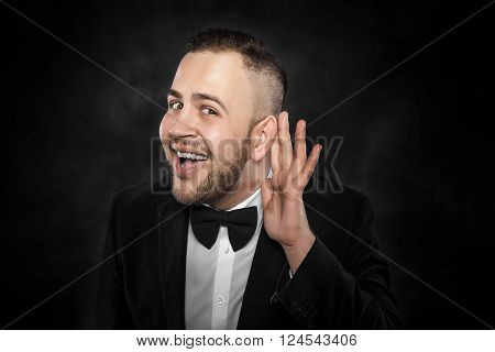 Man with big ear listening something on a dark background.