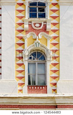 Old decorated window in the wall of a building