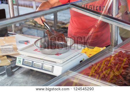 GEORGE TOWN MALAYSIA - MARCH 23: Woman weigh Chinese dried pork at the street market on March 23 2016 on George Town Malaysia.