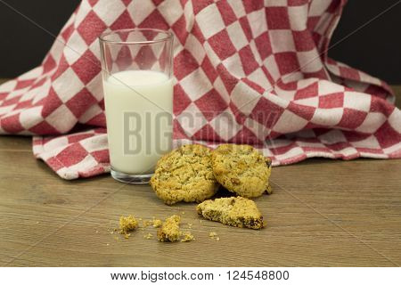 Homemade oat and raisin cookies with milk on a rustic background