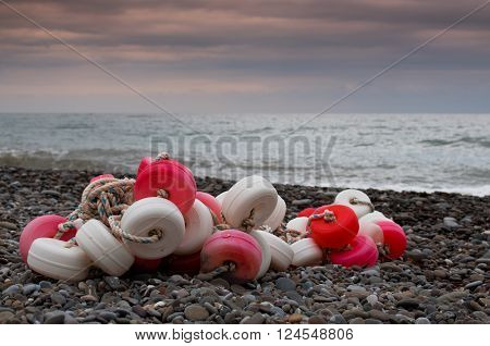 Red and white pile of fishing floats on the beach