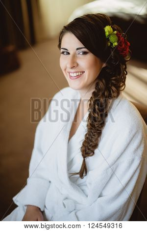 bride sits on a chair in a white robe in the room