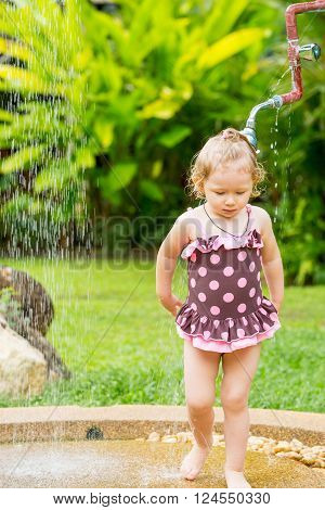 Cute little child girl in swimsuit bathing in the shower on tropical resort