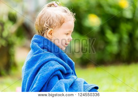 Child girl in towel after swimming basking in sun on tropical resort