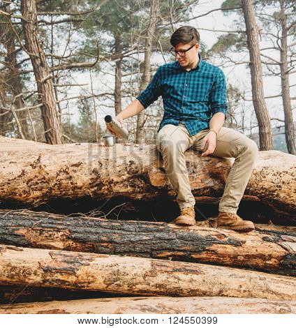 Traveler young man sitting on tree trunk and pouring tea from thermos to cup in the forest. Man has a picnic outdoor