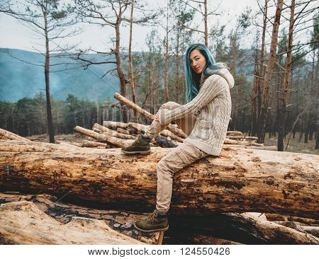 Beautiful young woman sitting on stack of felled tree trunks in the forest and looking at camera