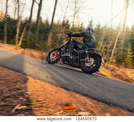 Young man riding chopper on road in forest